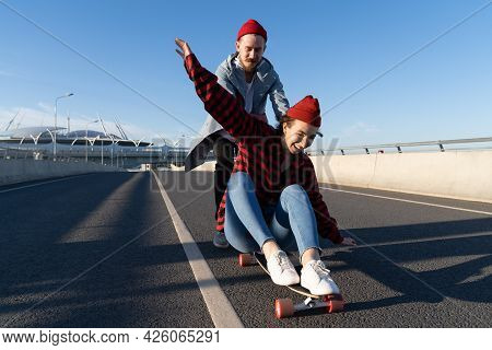 Stylish Man And Woman Longboarding Enjoy Time Together. Young Couple In Romantic Relationship Skatin