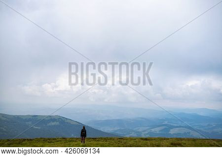 Girl With A Backpack In The Mountains. Low Clouds. Fog. Solitude With Nature. Loneliness. Freedom. T