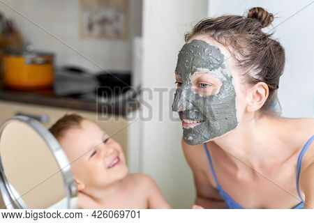 Young Adult Happy Beautiful Caucasian Woman With Little Son Applying Natural Gray Clay Face Mask At