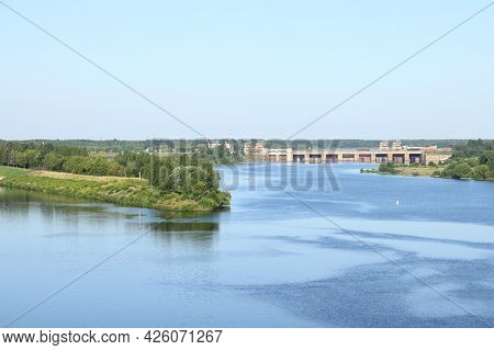 The Blue Water Surface Of The River With The Banks Overgrown With Greenery Against The Backdrop Of T
