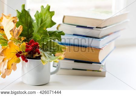 Autumn Composition With Stack Of Books And Bouquet Of Yellow Autumn Leaves And Sprigs Of Mountain As