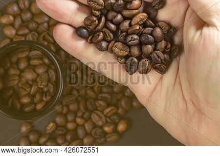 Fragrant Coffee Beans Of Quality Roasted Coffee In A Man Hand, Selective Focus, Copy Space.