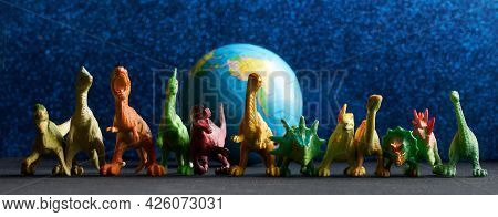 Toy Dinosaurs Stand Next To A Globe On A Blue Background. The Concept Of Protecting Planet Earth And