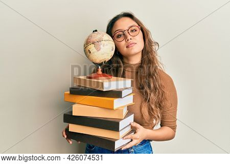 Young hispanic girl studying geography relaxed with serious expression on face. simple and natural looking at the camera.