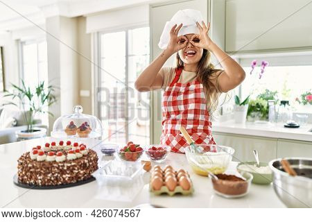 Beautiful young brunette pastry chef woman cooking pastries at the kitchen doing ok gesture like binoculars sticking tongue out, eyes looking through fingers. crazy expression.