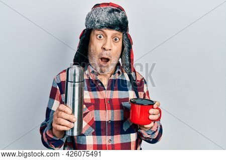 Handsome mature handyman wearing winter hat with ear flaps drinking hot coffee from thermo in shock face, looking skeptical and sarcastic, surprised with open mouth