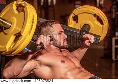 Muscular Man Workout With Barbell At Gym. Bodybuilder Athletic Man With Six Pack, Perfect Abs, Shoul
