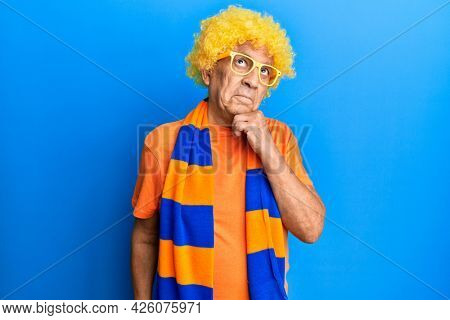 Senior hispanic man football hooligan cheering game thinking concentrated about doubt with finger on chin and looking up wondering