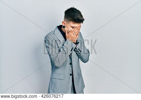 Young caucasian boy with ears dilation wearing business jacket with sad expression covering face with hands while crying. depression concept.