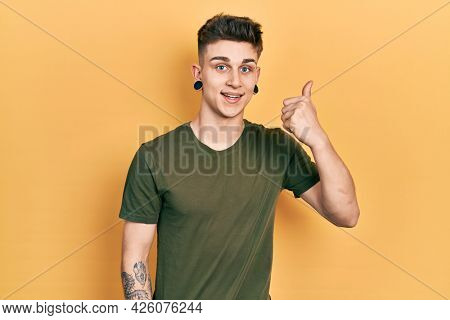 Young caucasian boy with ears dilation wearing casual green t shirt smiling happy and positive, thumb up doing excellent and approval sign