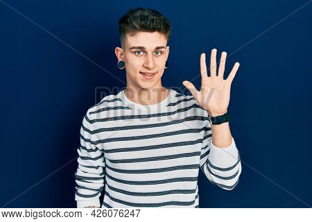 Young caucasian boy with ears dilation wearing casual striped shirt showing and pointing up with fingers number five while smiling confident and happy.