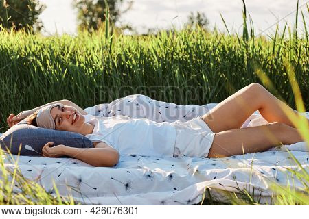Happy Female With Blindfold Over Forehead Lying In Soft Bed In Green Meadow, Looking Directly At Cam