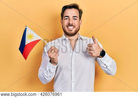 Handsome caucasian man with beard holding philippines flag smiling happy and positive, thumb up doing excellent and approval sign
