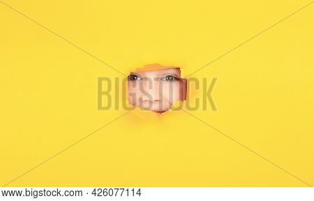 Kid With Toothy Smile Shows Face In Paper Hole. Positive Child With Toothy Pleasant Smile On Face, K