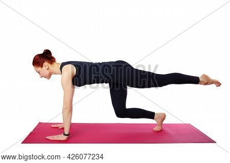 Pilates Or Yoga. This Slender Beautiful Woman Performs A Pilates Exercise On A Gym Mat. Isolated On