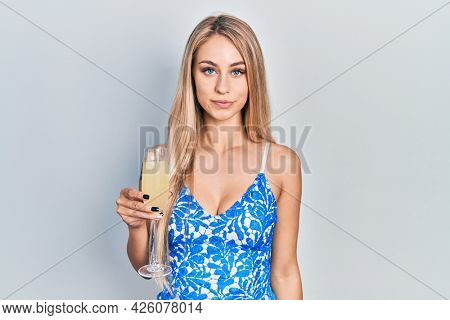 Young caucasian woman drinking a glass of sparkling champagne thinking attitude and sober expression looking self confident