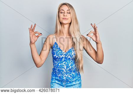 Young beautiful caucasian woman wearing summer dress relax and smiling with eyes closed doing meditation gesture with fingers. yoga concept.