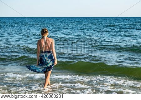 Young Woman In A Swimsuit And Pareo Walks Into The Sea - View From The Back. Real Adult Girl On A Ba