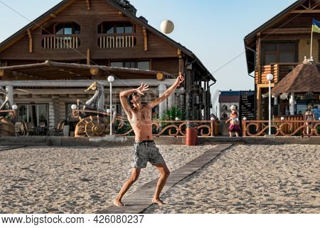 A Young Man Kicks A Ball With His Hand While Playing Beach Volleyball In Zaliznyi Port (ukraine). Th