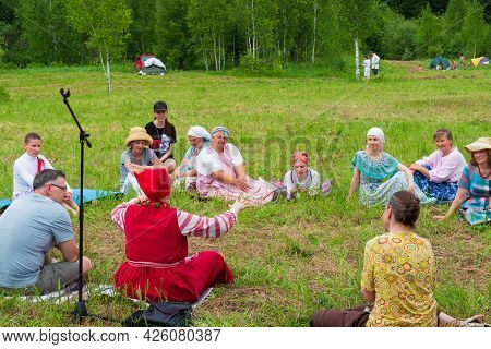 Krasnoyarsk, Russia - June 19, 2021: People Sit Around In A Forest Glade And Listen To The Storytell