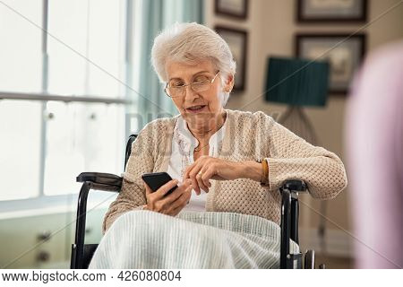 Elderly woman sitting on wheelchair using smart phone with some difficulty. Confused old disabled woman messaging on cellphone at nursing home. Senior patient using mobile phone to communicate.