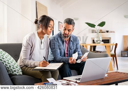 Mature couple calculating bills at home using laptop. Multiethnic couple working on computer while calculating finances. Mature indian man with african american woman at home analyzing their finance.