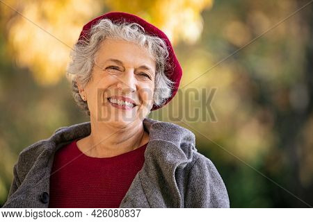 Portrait of senior woman smiling outdoor. Cheerful old woman in autumn park with copy space. Happy retired lady with grey hair and red beret smiling and looking away.