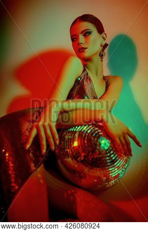 Stunning fashion model girl posing in a shiny evening dress with a mirrored disco ball. Fashion shot. Ballet show. Studio portrait in mixed light.