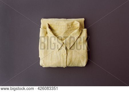 Neatly Folded Yellow Shirt On A Gray Background, Top View