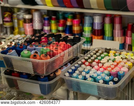 Multi-colored Bobbins Of Sewing Thread In Plastic Boxes In The Foreground. In The Background, On The