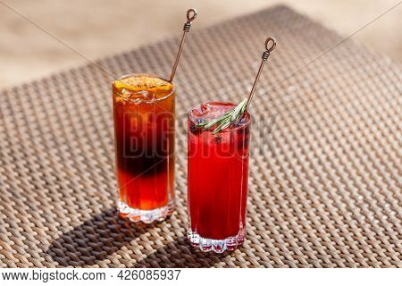 Two Fruit Cocktails Standing On The Table In Summer Sunny Day, Refreshing Drinks. Iced Berry Mocktai