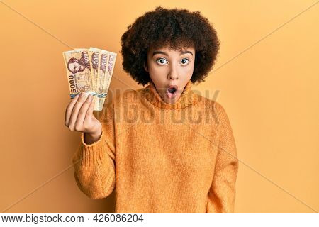 Young hispanic girl holding 5000 hungarian forint banknotes scared and amazed with open mouth for surprise, disbelief face