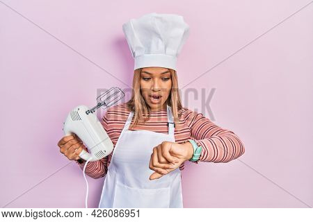 Beautiful hispanic woman holding pastry blender electric mixer looking at the watch time worried, afraid of getting late