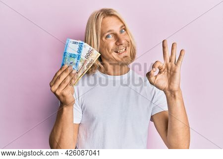 Caucasian young man with long hair holding hungarian forint banknotes doing ok sign with fingers, smiling friendly gesturing excellent symbol