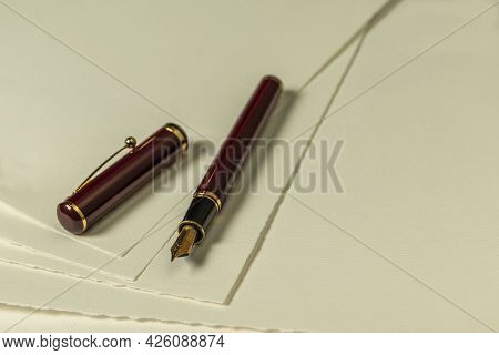 Dark Red Fountain Pen With Gold Nib And Loose Cap On A Number Of Sheets Of Cream Colored Paper As Ba
