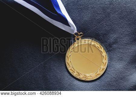 Gold medal on velvet cushion.