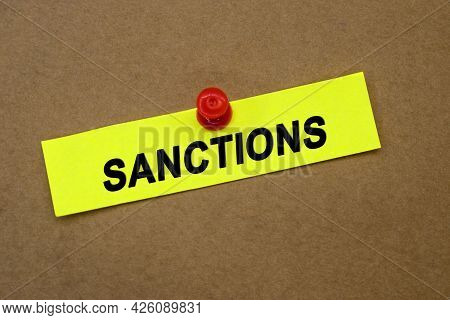 The Word Sanctions Is Written On A Yellow Sheet That Is Attached By A Button To A Brown Background.