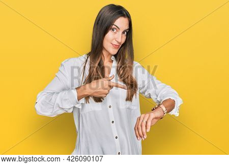Young beautiful woman wearing casual clothes in hurry pointing to watch time, impatience, upset and angry for deadline delay