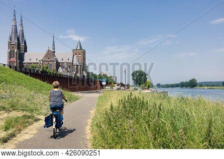 Woman Cycling Along River Meuse Near Dutch Village Cuijk With View At Historic Martinus Church