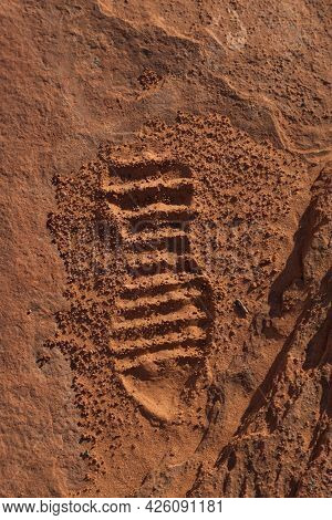 The Impression Of The Bottom Of A Hiking Shoe Left In The Fine Grains Of Orange Sand On A Walking Pa