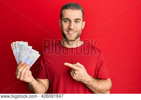Young caucasian man holding swedish krona banknotes smiling happy pointing with hand and finger