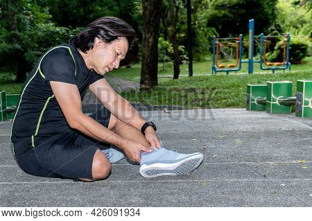 Asian Man Is Currently Having A Ankle Injury During Her Exercise By Running In The Running At The Pa