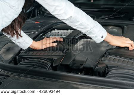 Young Woman Standing In Front Of The Car With Opened Hood Looking Under Car Hood
