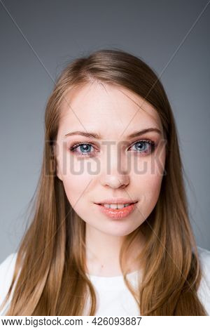 Portrait Of A Beautiful Young Girl Flirting And Looking At The Camera While Standing On A Gray Backg