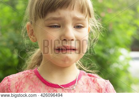 Portrait Of A Small, Fair-haired Girl Who Is Crying In The Open Air