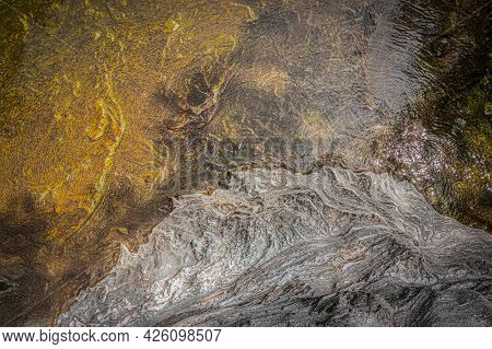 Top view of the water of a river and a rock bank. The wind gives the whole a superb texture.