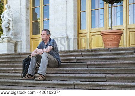 An Adult Caucasian Pensioner In Summer Clothes Sits And Rests On The Steps Of An Old Historical Hous