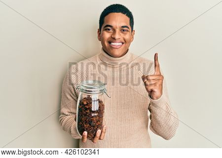 Young handsome hispanic man holding jar full of raisins smiling with an idea or question pointing finger with happy face, number one
