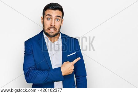 Young hispanic man wearing business jacket pointing aside worried and nervous with forefinger, concerned and surprised expression
