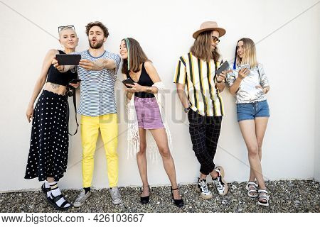 Young Stylish People Having Fun, Standing Together With Smart Phones On A White Wall Background. Dep